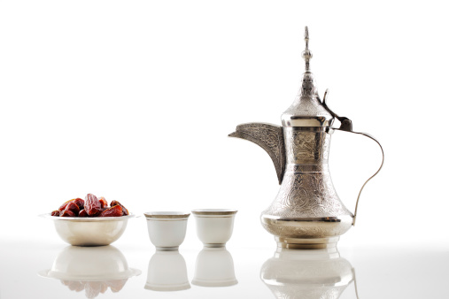 A silver teapot with Arabic dates and cups