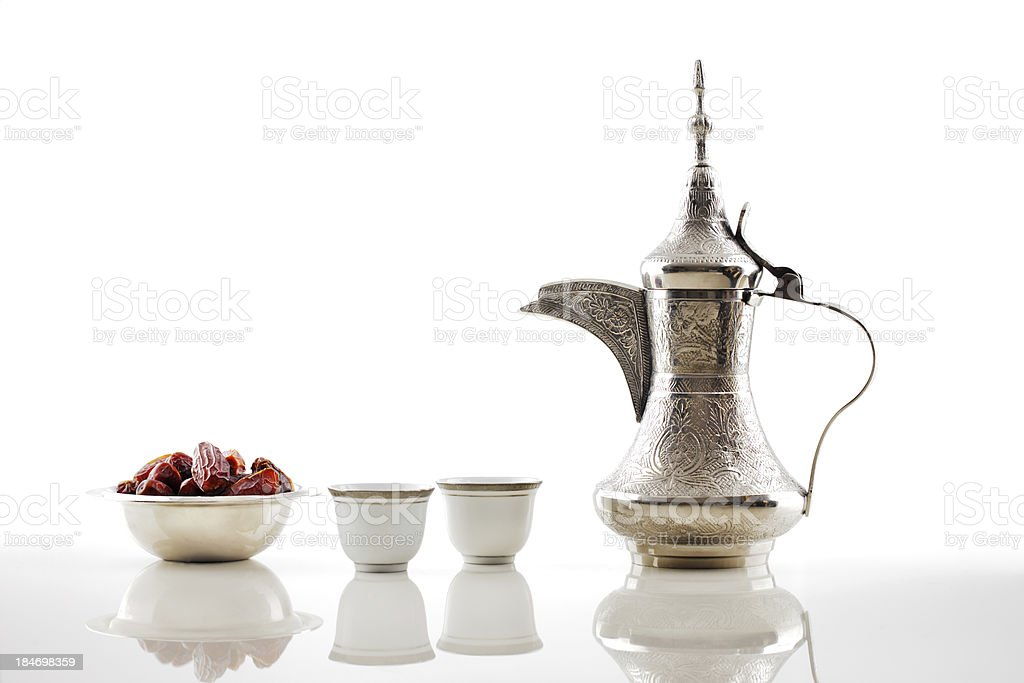 A silver teapot with Arabic dates and cups stock photo