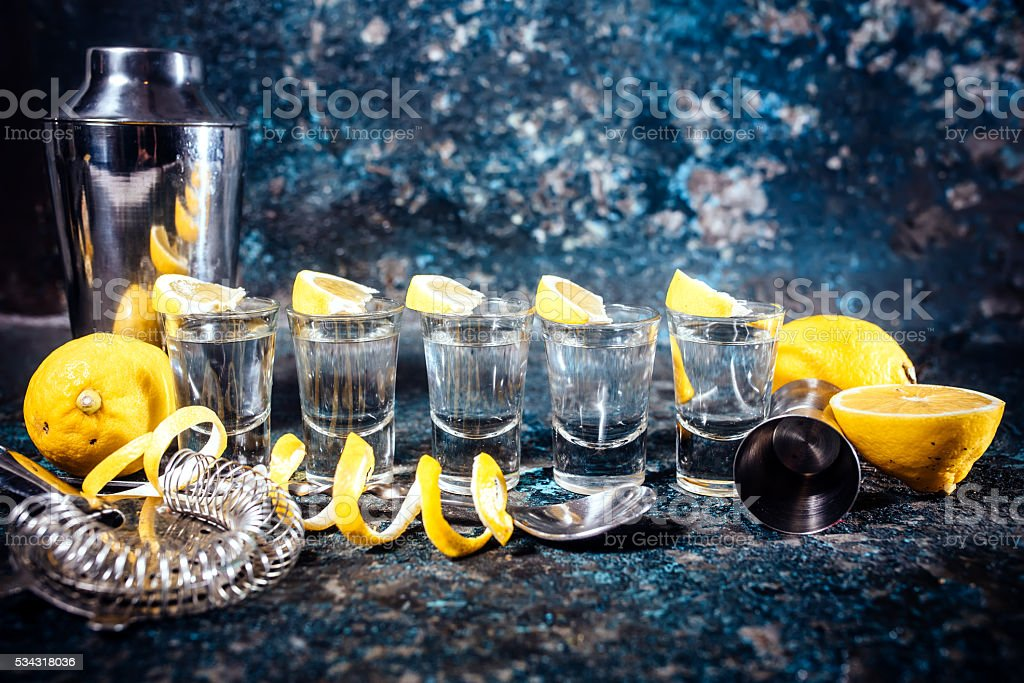 Silver tequila shots with lemon slices and cocktail elements. stock photo