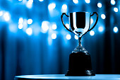 istock Silver Trophy competition in the dark on the abstract blurred light background with copy space, Blue Tone 1249117045