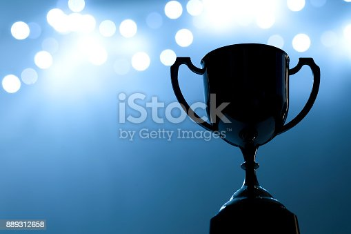 istock Silver Trophy competition in the dark on the abstract blurred light background with copy space, Blue Tone 889312658