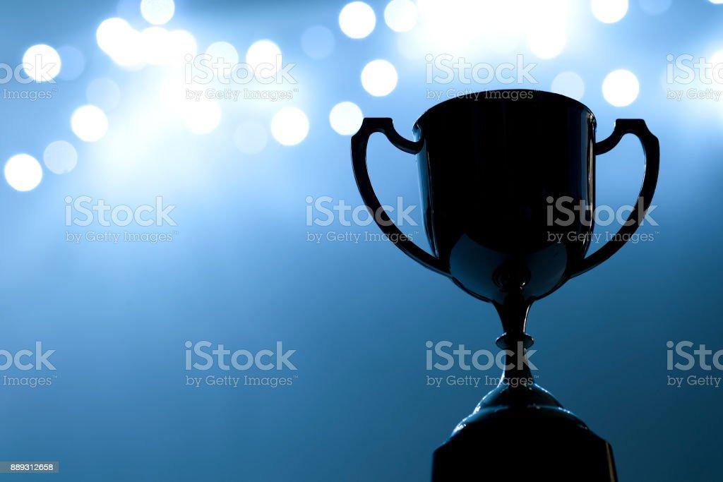 Argent concours trophée dans le noir sur le fond clair flou abstrait avec espace copie, ton bleu - Photo