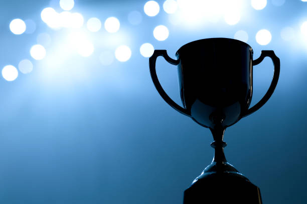 silver trophy competition in the dark on the abstract blurred light background with copy space, blue tone - trophy award stock photos and pictures