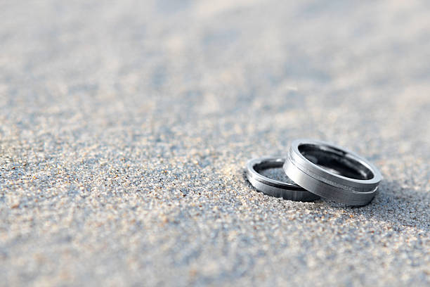Silver wedding rings on the sand on a beach stock photo