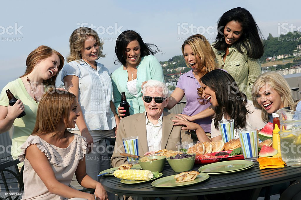 Silver-haired man in sunglasses in the center of young girls royalty-free stock photo