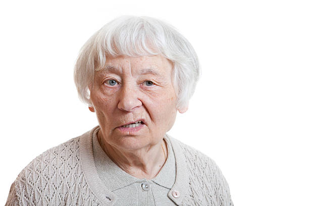 Silver-haired older woman with an annoyed facial expression stock photo