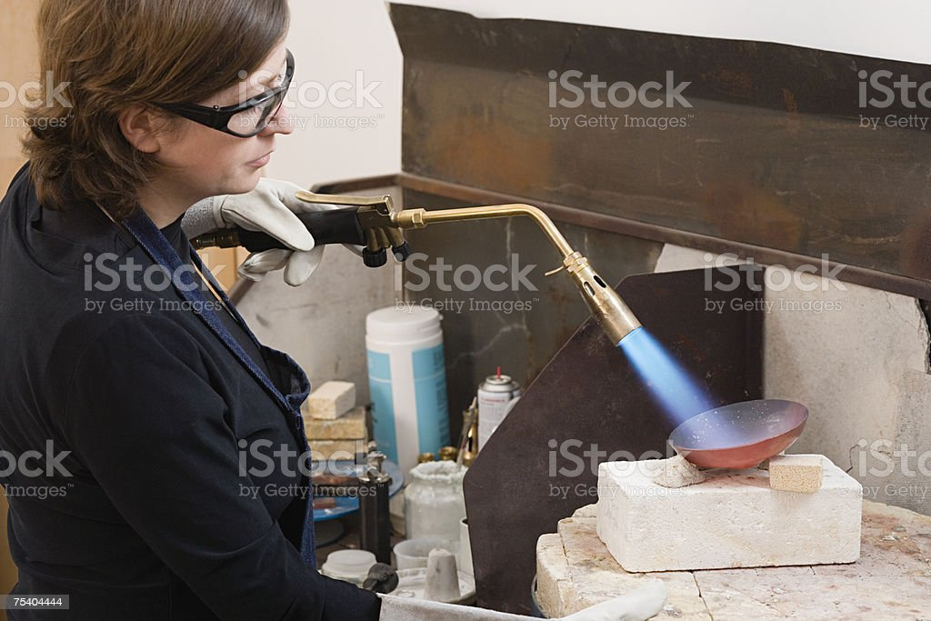 Silversmith using blow torch stock photo
