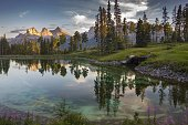 Peaceful Pond in Famous Silvertip Golf Course above Town of Canmore with Reflections of Three Sisters Mountain near entrance to Banff National Park in Rocky Mountains Alberta Canada