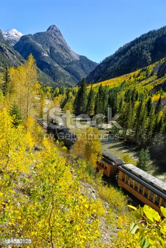 Silverton Durango Railroad.  Scenic area along the Animas RIver with narrow-gauge train in steep rugged mountain canyon.  Scenic route with autumn fall colors and sunny blue-sky day.  Captured as a 14-bit Raw file. Edited in ProPhoto RGB color space.