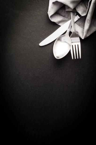 Silverware and napkin shot directly above on dark background stock photo