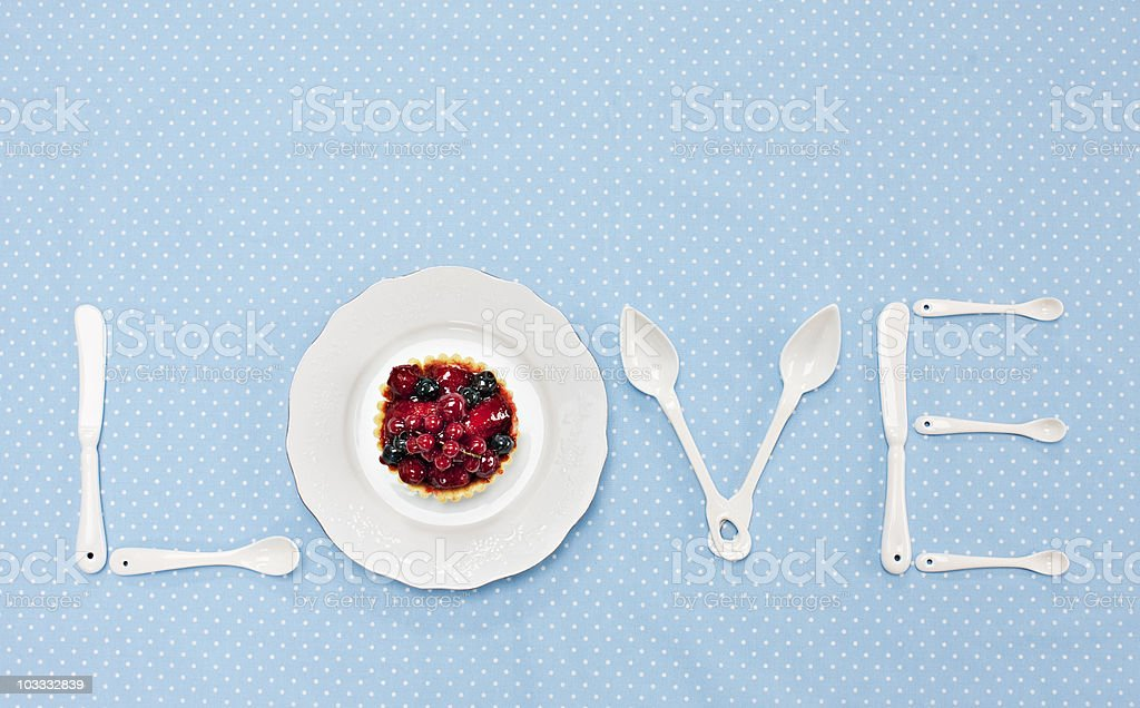 Silverware and plate with tart spelling 'love' on tablecloth stock photo