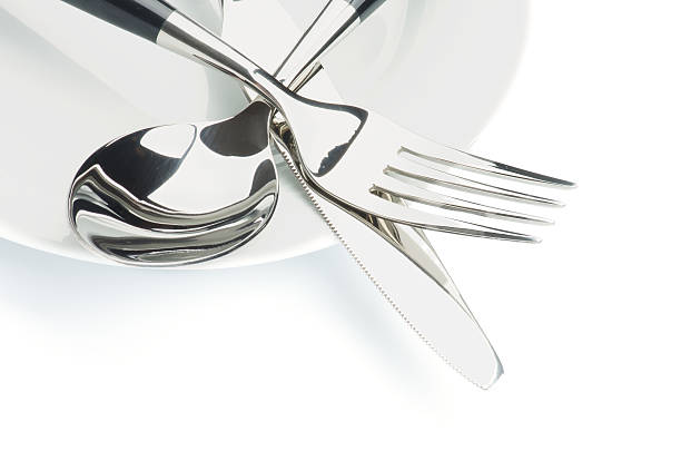 Silverware stacked in a pile on a white plate stock photo
