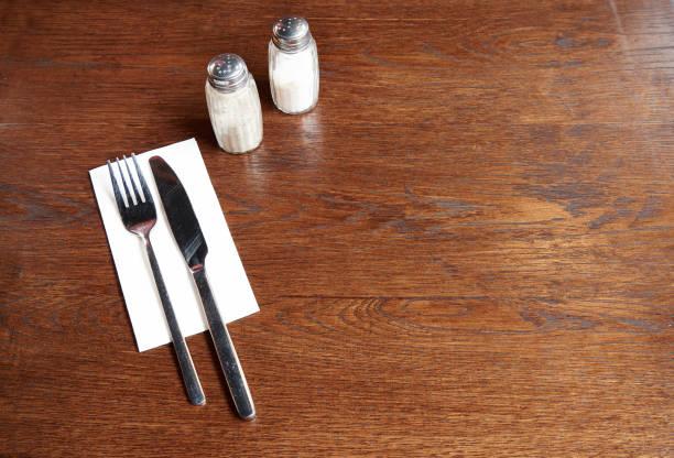 zilverwerk met zout en peper op een rustieke pubtafel - zout smaakstof stockfoto's en -beelden