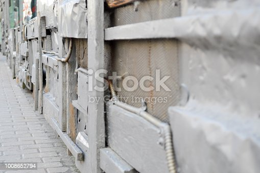 Silvery texture in steampunk style, cyberpunk with bent, twisted, old metal sheets of tin, bolts, rivets, iron rods and corrugated wires and a grid. The background.
