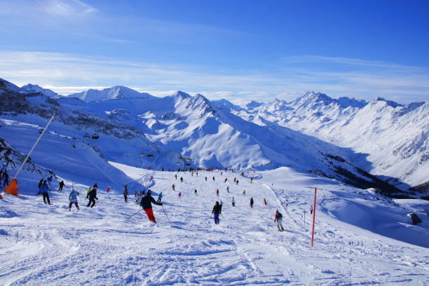 Silvretta Ischgl Samnaun Ski resort and mountain range Silvretta Ischgl Samnaun Ski resort and mountain range. Snow covered skiers at slope in winter pejft stock pictures, royalty-free photos & images