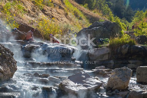 Here is a ground level view of the Diamond Fork Hot Springs showing a couple of bathers and steam rising from the water.  From the red marks on the guy's skin, the water is quite hot and he looks to have been in it for too long.  This shot was taken in the morning, just as the rising sun was clearing the surrounding mountains. Fall colors are in full bloom in the background.