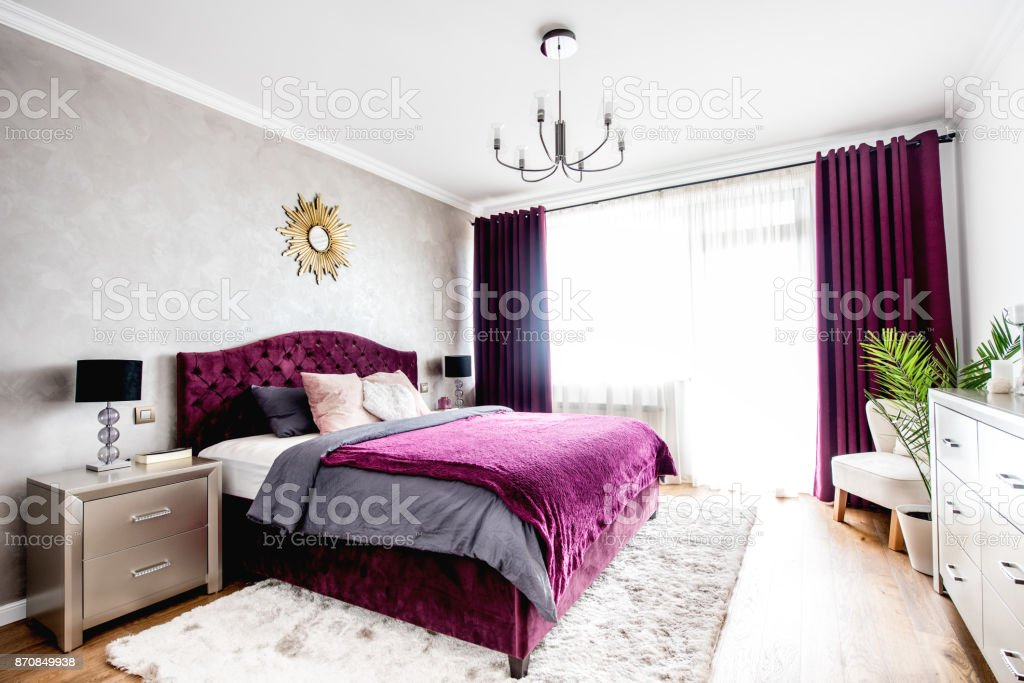Simple and stylish bedroom interior with double bed, purple bedding and modern nightstands stock photo