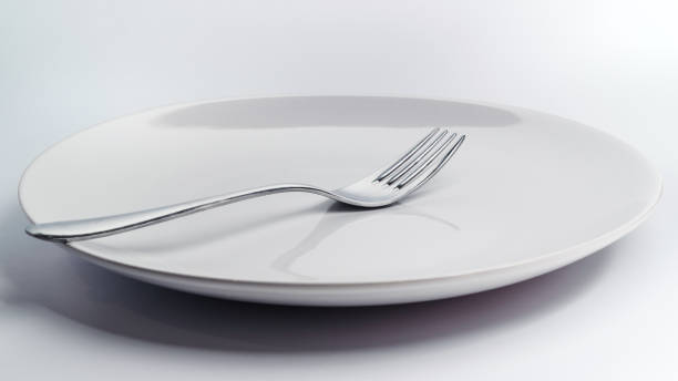 A simple and white empty crock dish for eating on a white uniform background with elegant steel cutlery like a fork A simple and white empty crock dish for eating on a white uniform background with elegant steel cutlery like a fork feeding frenzy stock pictures, royalty-free photos & images