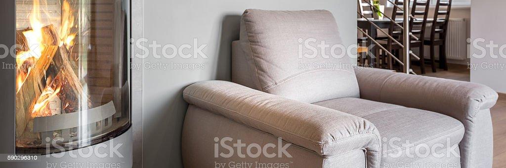 Simple armchair next to fireplace royaltyfri bildbanksbilder