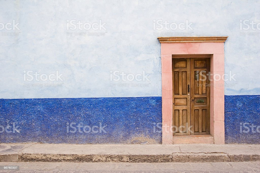 Simple Blue Wall with Wood Door in Mexico royalty-free stock photo
