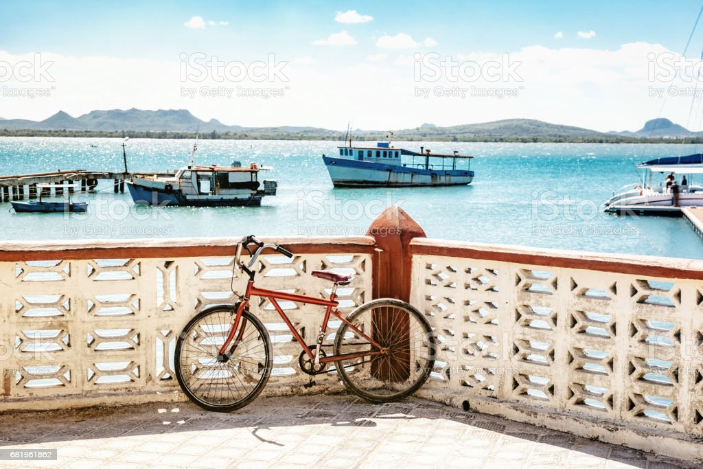 simple bycicle at the bay of Gibara in Cuba with boats in background stock photo