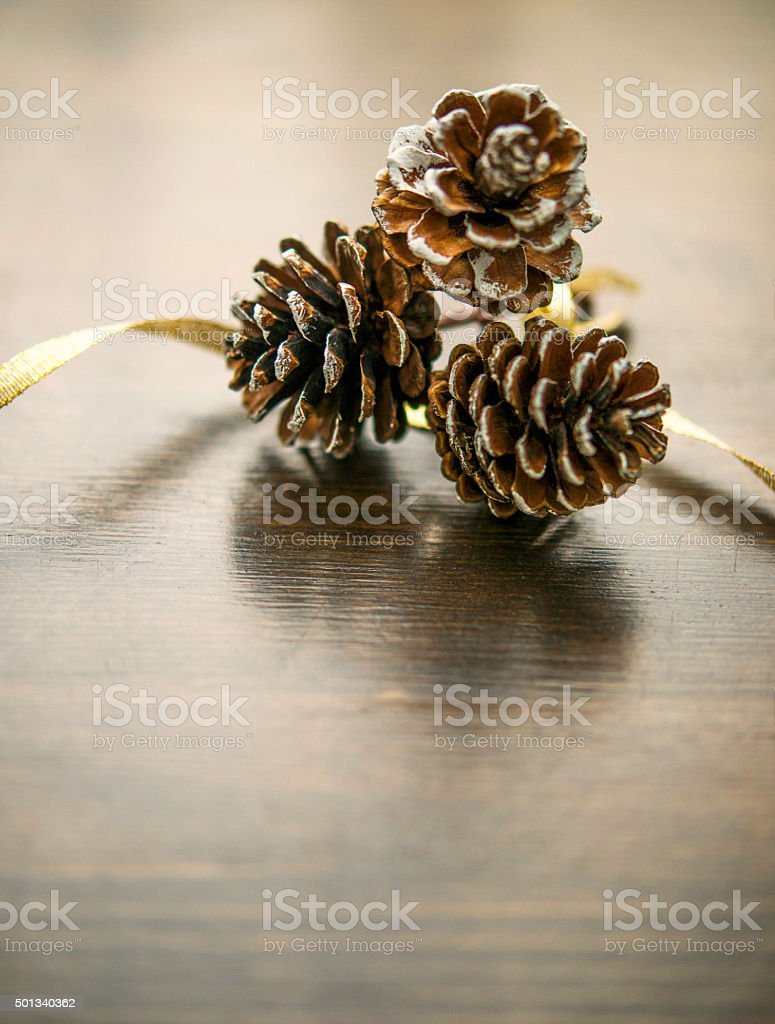 simple christmas background with pinecones and gold ribbon royalty free stock photo