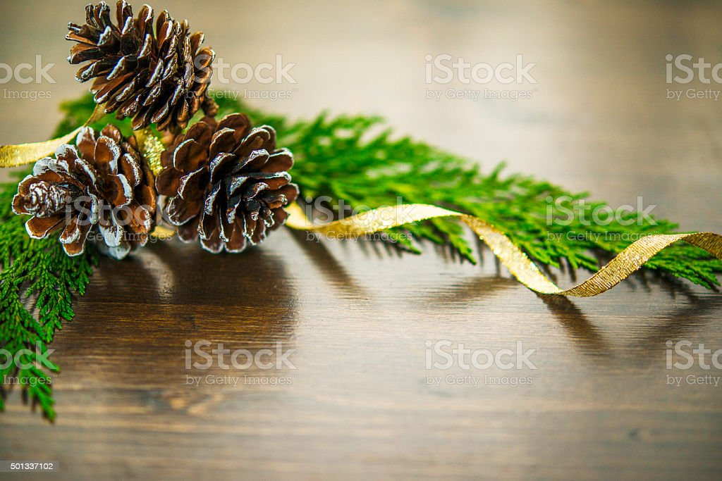Simple Christmas background with pinecones, evergreen leaves and gold ribbon stock photo