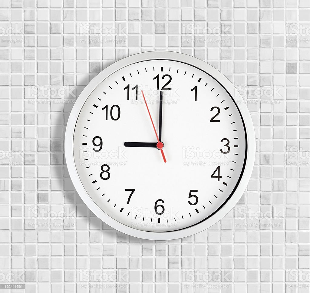 Simple clock or watch on white tile wall displaying nine stock photo