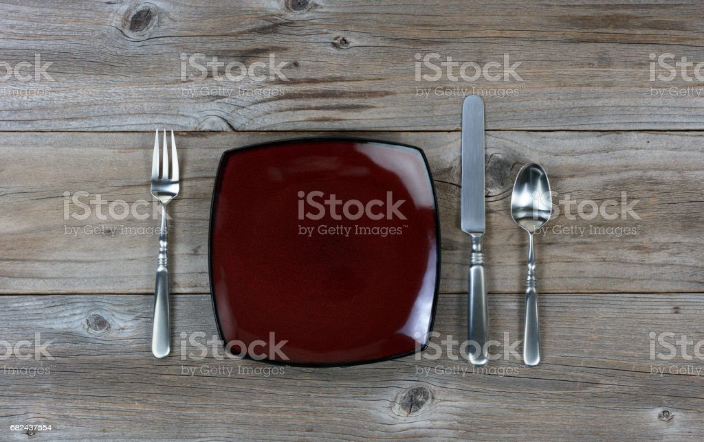Simple dinner and silverware setting on rustic wood background royalty-free stock photo