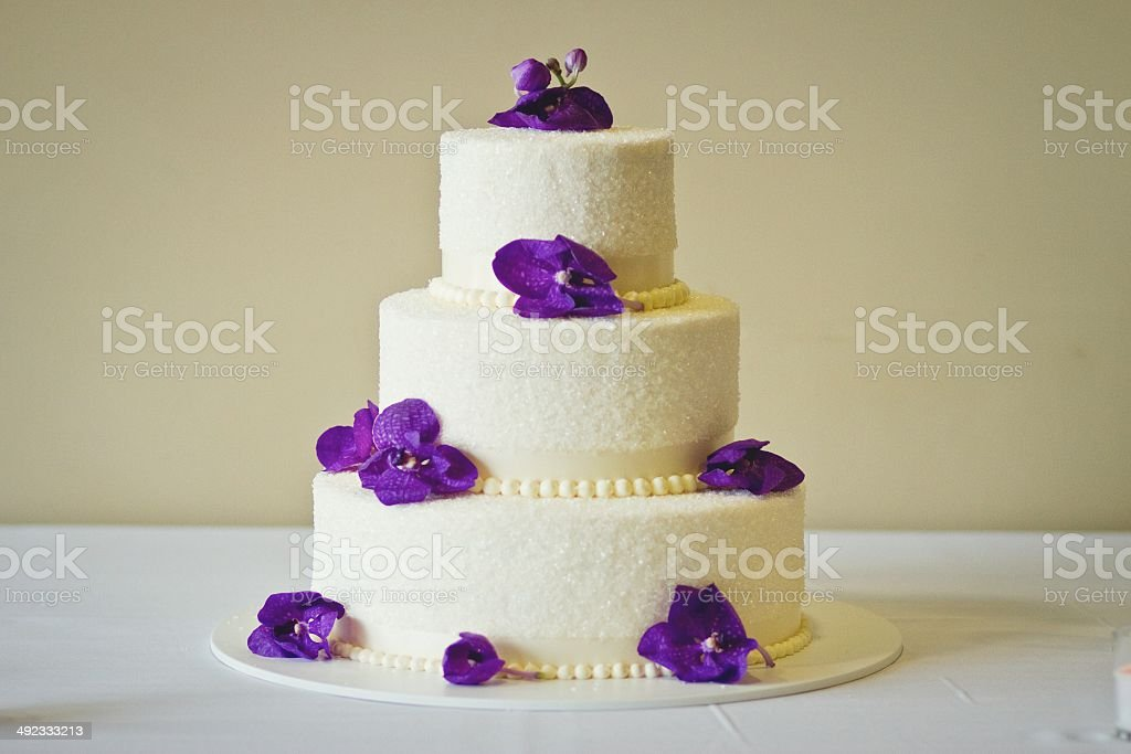 An elegant catered white wedding cake with 3 tiers and purple flowers