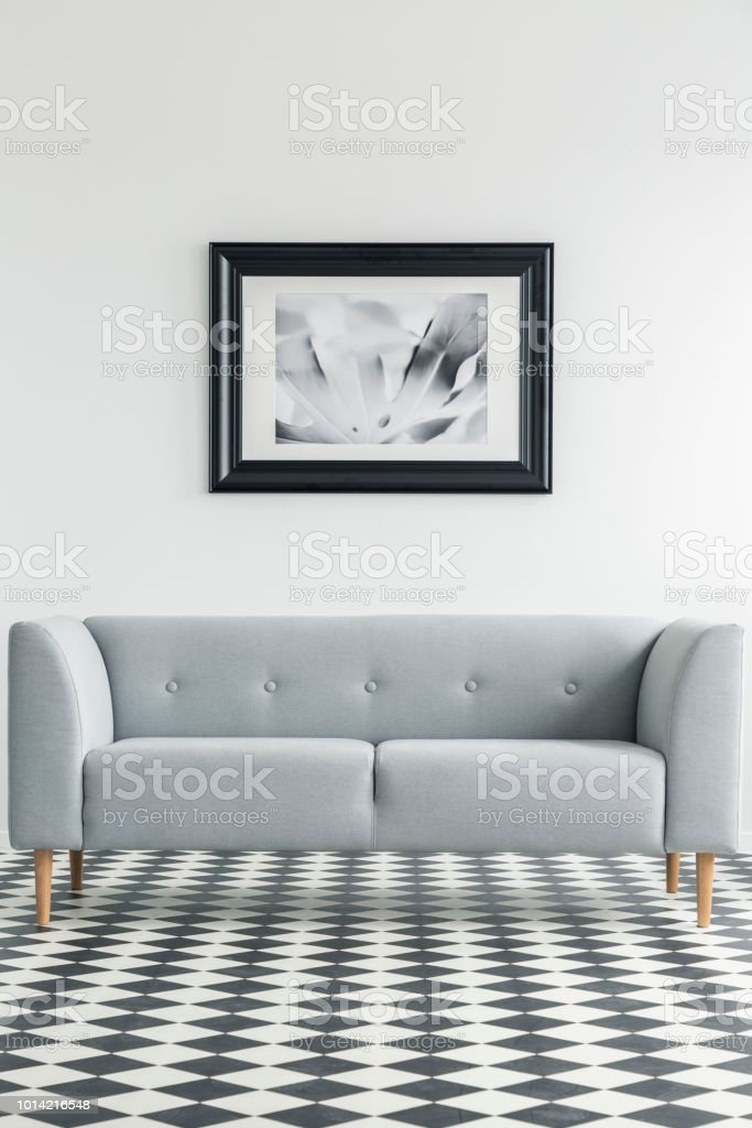 Simple, grey sofa on a checkered floor with a painting in the backgorund in a living room interior. Real photo stock photo