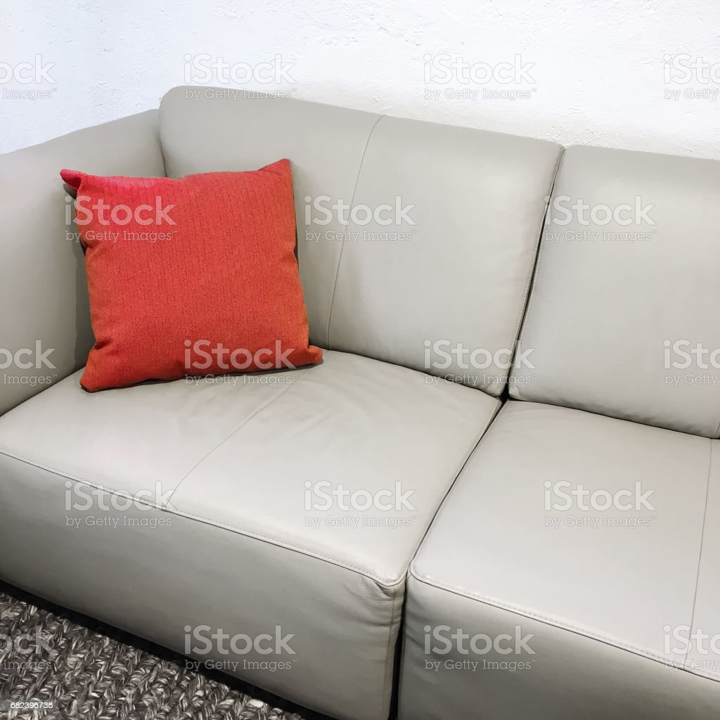 Simple leather sofa with red cushion royalty-free stock photo