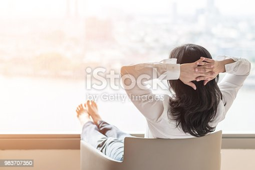 istock Simple life style relaxation with Asian working business woman healthy lifestyle take it easy resting in comfort hotel or home living room having free time with peace of mind and self health balance 983707350