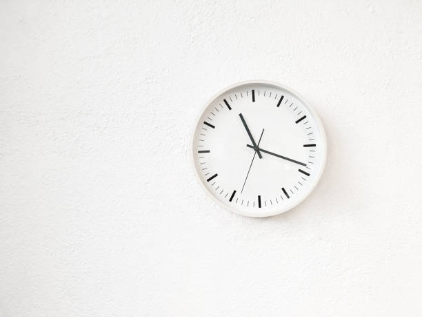 Simple modern round clock on white wall stock photo