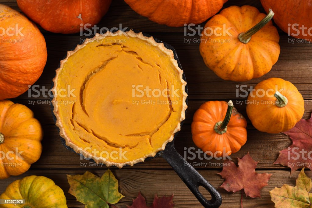 Simple pumpkin pie in cast iron pan decorated with bright orange pumpkins and marple leaves on rustic background stock photo