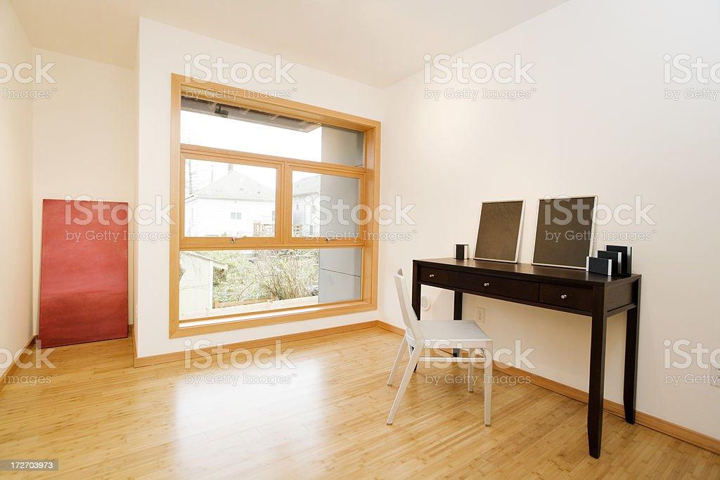 Chambre simple avec parquet en bois dur et de grandes fenêtres
