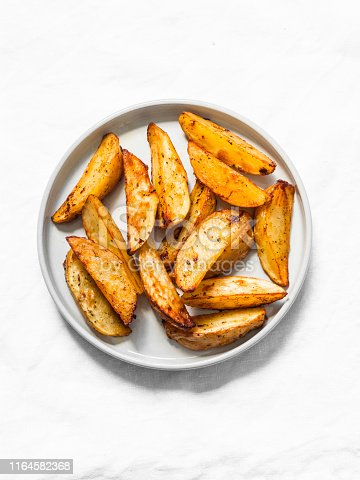 Simple rustic baked potato slices on a light background, top view