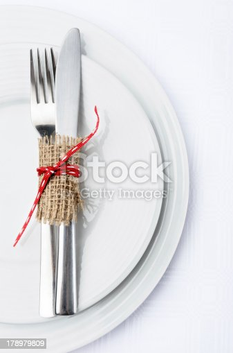 Dinner setting with white plates crockery and silver cutlery tied with hessian and a red ribbon bow, simple rustic elegant table decor