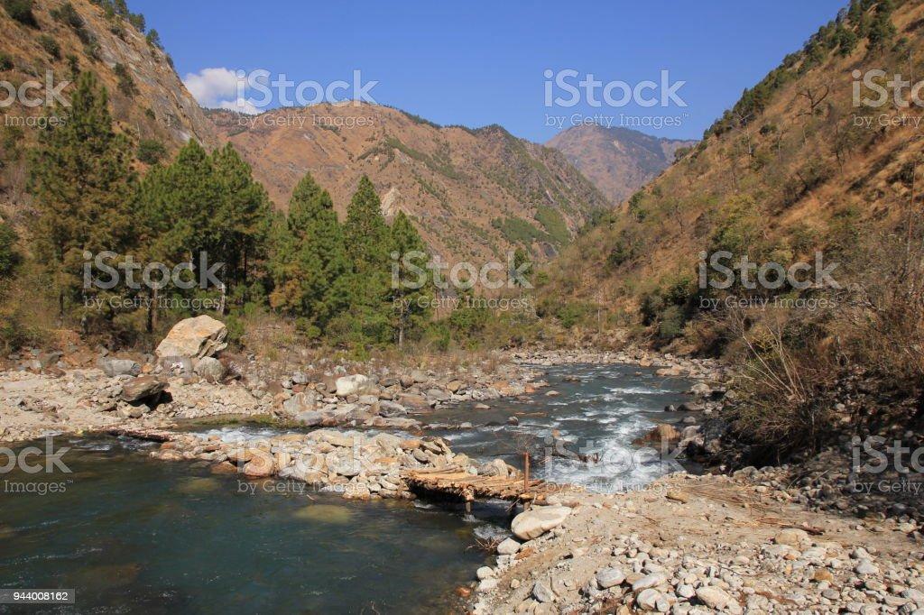 Simple timber bridge and Langtang Khola, river in Nepal. stock photo