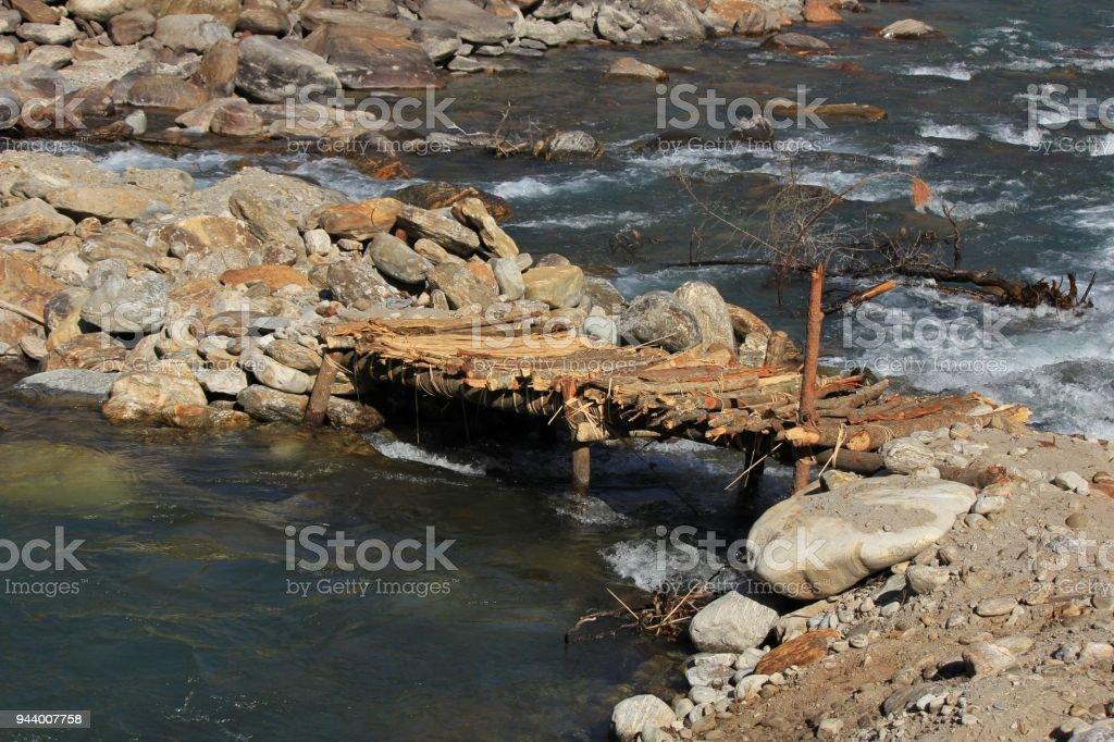 Simple timber bridge over Langtang Khola, river in Nepal. Scene near Shyaphru Besi. stock photo