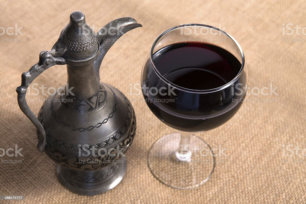 Simple View Of Pewter Flagon and Red Vine Glass royalty-free stock photo