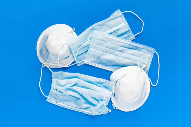 simple white air protection mask on the color surface stock photo