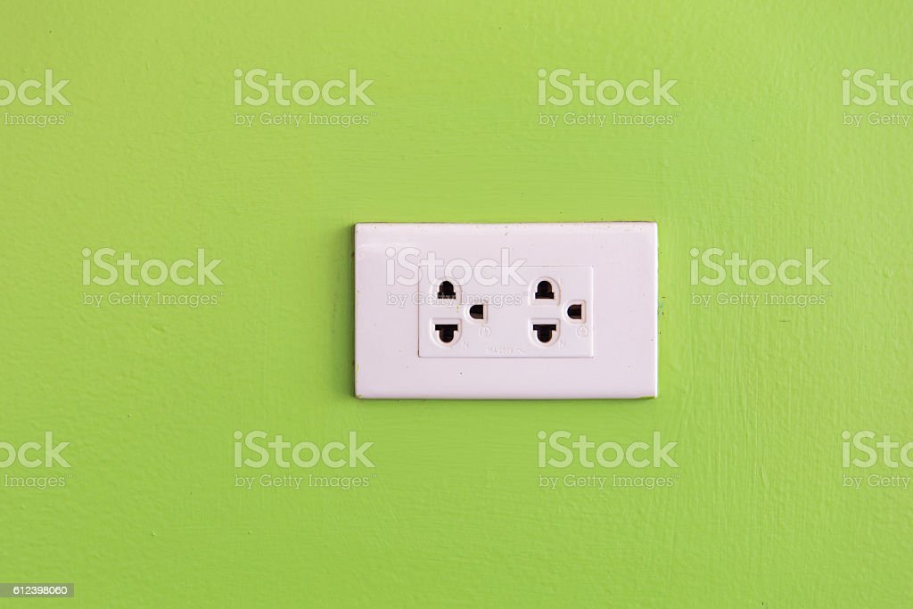 simple white electric usa socket on green wall stock photo
