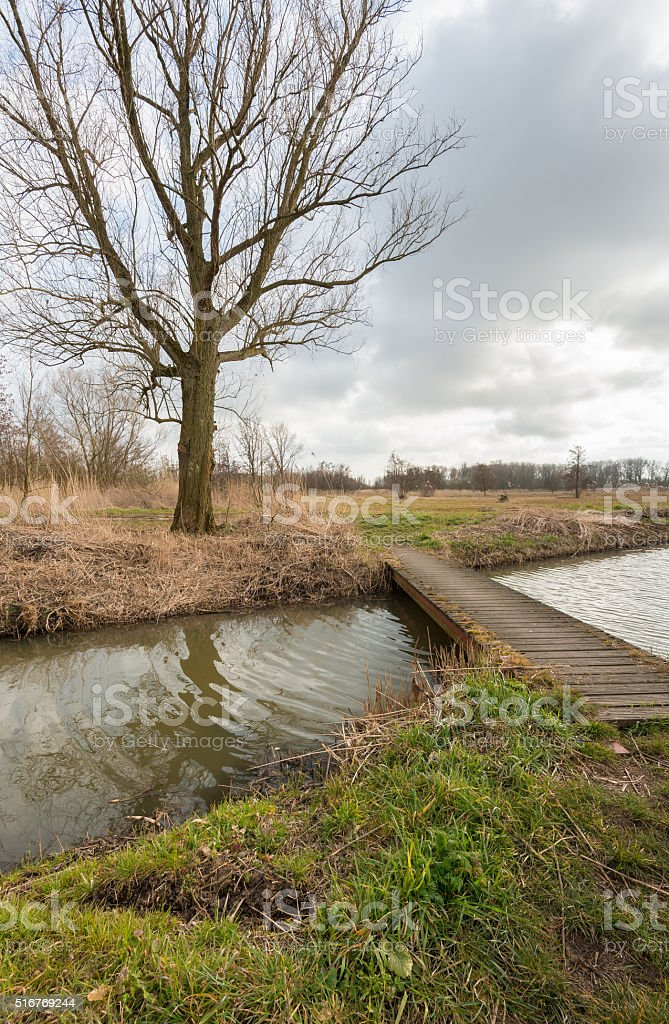 Simple wooden bridge made of boards across a stream stock photo