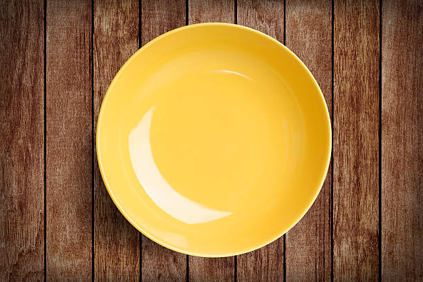 Simple yellow circular porcelain plate on wood with clipping path – Foto