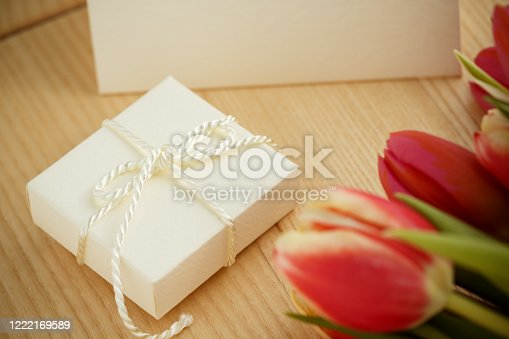 Selective focus of plain white package placed on top of wooden table for a birthday gift. Red tulips bouquet is visible on the foreground.