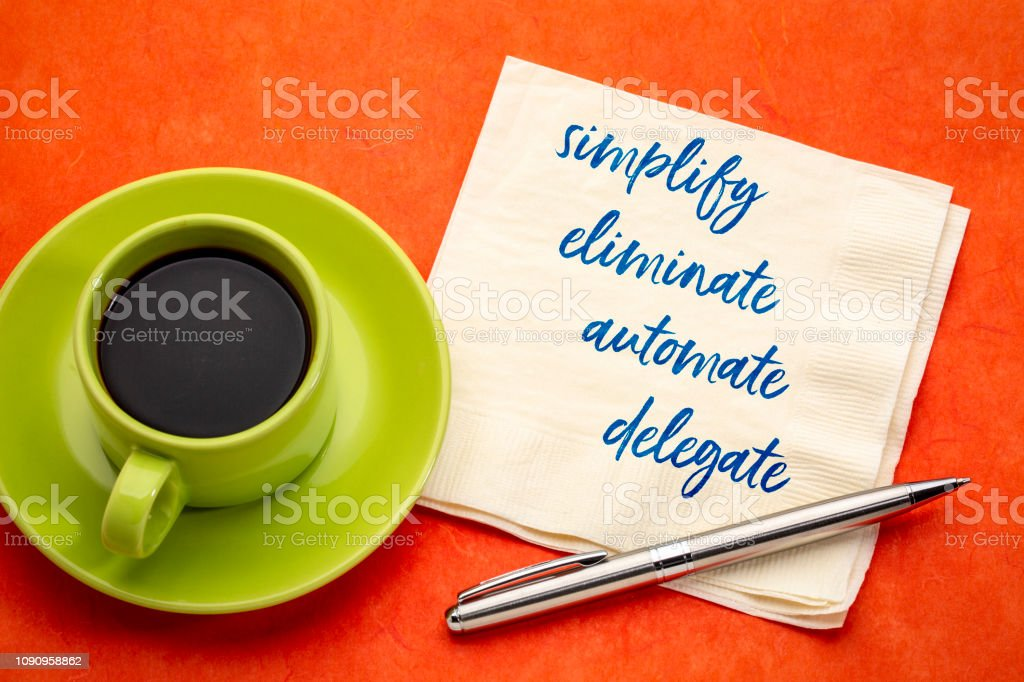 simplify, eliminate, automate, delegate concept on napkin stock photo