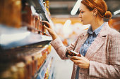Young woman holding a jar of Sun-dried tomatoes in supermarket. She's searching for specific manufacturer.