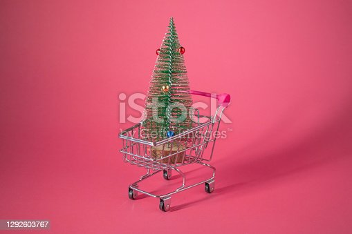 Simply flat lay design small supermarket grocery push cart for shopping with wheels whit christmas tree