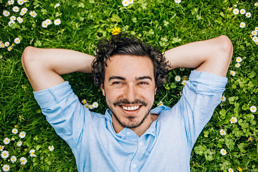 Smiling young man lying down on a green grass with daisies